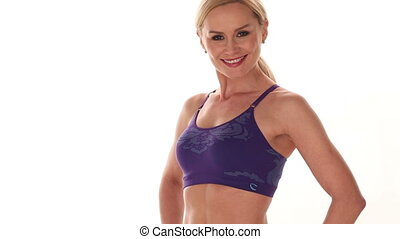 Fit confident young blond woman posing in her sportswear...