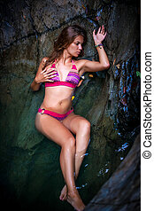 Beautiful sexy model posing in water of waterfalls wearing...