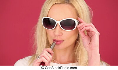 Young woman smoking an e-cigarette - Vivacious young blond...