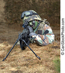 Sniper in foxhole - A camouflaged military sniper in a...