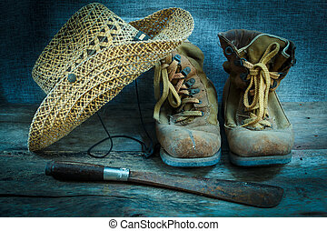 Old work boots, still life - old brown leather shoes on old...