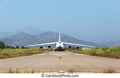 White heavy cargo jet with four engines ready to take off in...