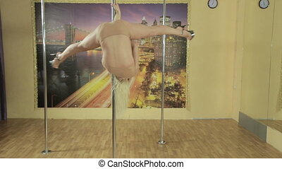 Seductive blonde performs gymnastic tricks on pole -...