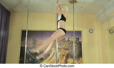 Attractive girl skillfully perform tricks on pole -...