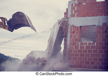 Mechanical digger demolishing the wall of a brick building -...