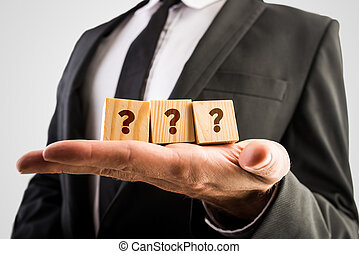 Three wooden cubes displaying question marks - Businessman...