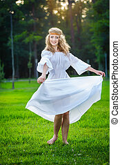 Young woman dancing in a park Girl in a meadow dancing on...