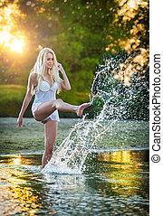 Girl splashing water at beach