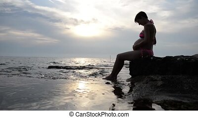 Pregnant woman in a swimsuit sitting in profile cradling her...