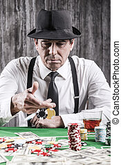 Playing poker. Serious senior man in shirt and suspenders throwing his gambling chips at the poker table