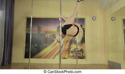Young blonde woman trains on pole - Young blonde heeled pole...