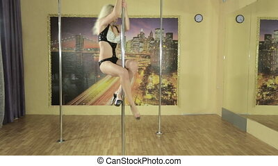 Girl performs different tricks on pole - Attractive girl...
