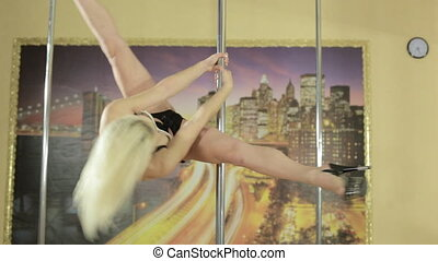 Attractive young woman doing acrobatic tricks on pole -...