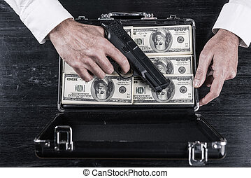 Illegal business. Top view of man holding gun and opening a...