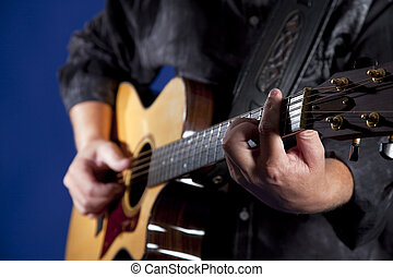 Guitar Player - Hands playing a guitar isolated on a blue...