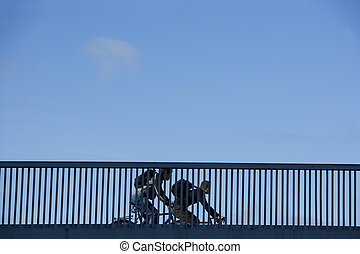 Bicycle Commuters on a Railing of bridge