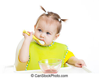 Baby eating with appetite sitting at table isolated
