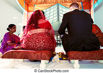 Indian Wedding Ceremony - Bride and Groom taking part in a...