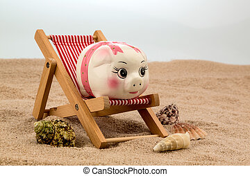 beach chair with piggy bank on the sandy beach symbolic...