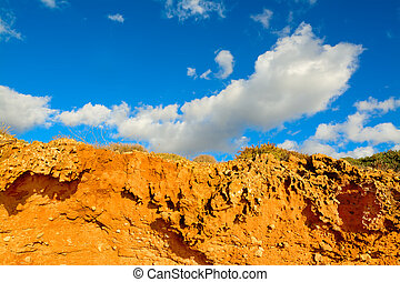 red soil under a blue sky with clouds. Shot in Alghero,...