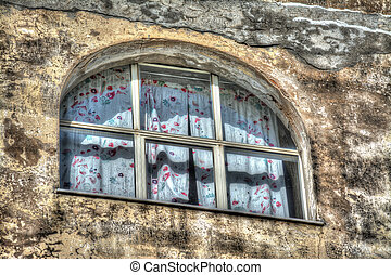 old window with curtain in a rustic wall