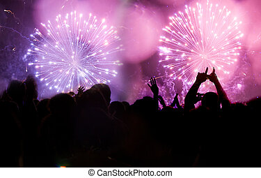 New Year concept - fireworks and cheering crowd celebrating...
