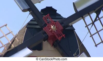 Dutch Windmill milling with open sails and shutters - close...