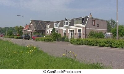 River dike, dwellings + traffic in Dutch river landscape -...