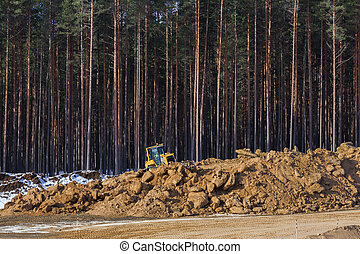 Yellow excavator at work in winter forest