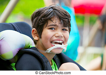 Disabled eight year old boy in wheelchair smiling - Handsome...