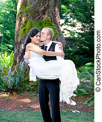 Caucasian groom carrying his biracial bride outdoors, with a...