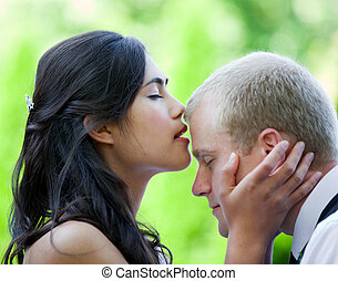 Bride kissing groom on forehead
