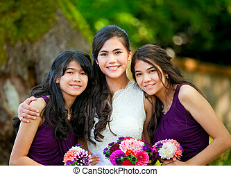 Bride with her two bridesmaid holding bouquet outdoors...