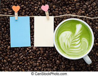 beautiful green tea and clip note on coffee bean background