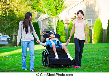 Disabled little boy in wheelchair walking with sisters on glassy