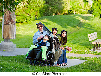 Disabled boy in wheelchair with family outdoors on sunny day...
