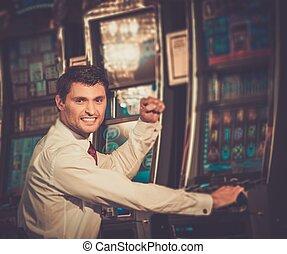 Handsome happy brunette man in white shirt near slot machine