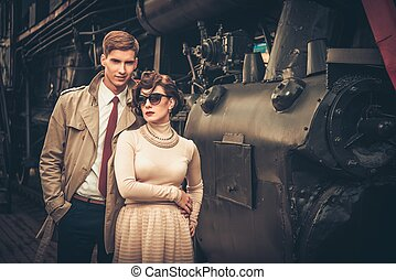 Vintage style couple near steam locomotive