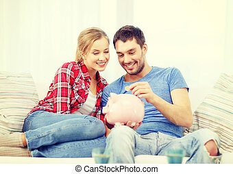 smiling couple with piggybank sitting on sofa - money, home,...