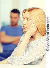 upset young woman with man on the back at home