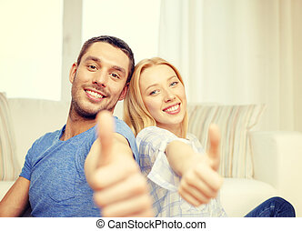 smiling happy couple at home showing thumbs up - love,...