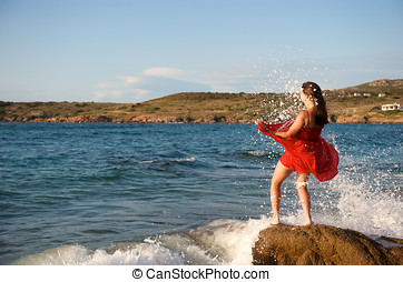 Pretty girl splashing by ocean wave - Pretty girl splashing...