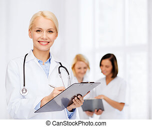 smiling female doctor with clipboard - healthcare and...