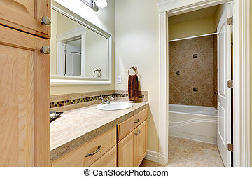 Light tones bahtroom vanity cabinet with tile counter top,...