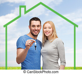 smiling couple holding key over green house - love, home,...