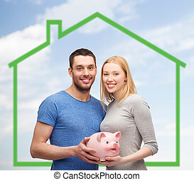 smiling couple holding piggy bank over green house - love,...