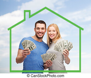 smiling couple holding money over green house - love, home,...