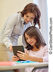 little girl with teacher and tablet pc at school -...