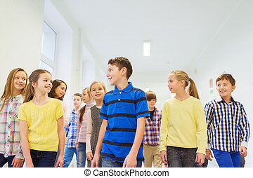 group of smiling school kids walking in corridor -...