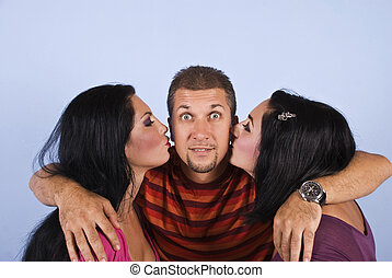 Amazed happy man with kissing women - Amazed man with beard...
